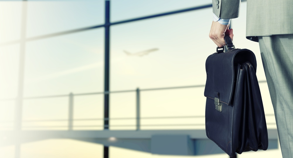 Back view of businessman at airport with suitcase in hand
