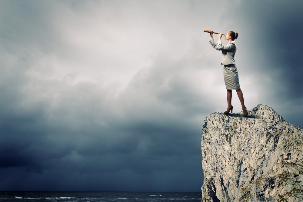 Image of businesswoman looking in telescope standing atop of rock.jpeg