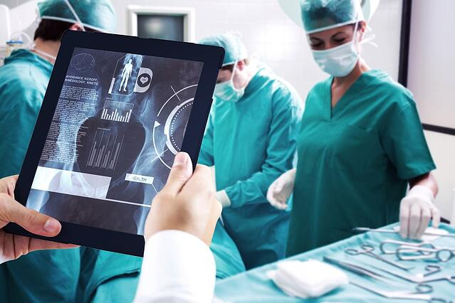 Man using tablet pc against medical interface on xray.jpeg