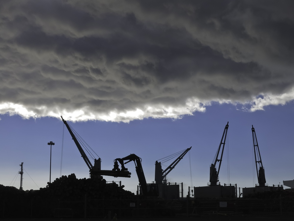 Storm cloud over silhouettes of cranes lifting logs to be shipped from seaport of Astoria, Oregon.jpeg